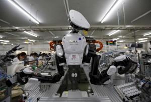 روبوت يشتغل مع عمال في خط التجميع في معمل في اليابان
